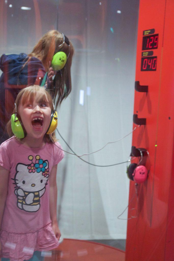 Flicka som skriker brevid en decibelmätare.