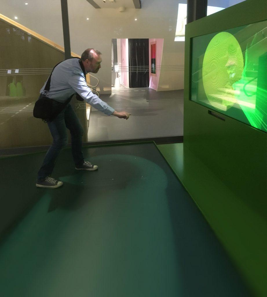Person i grön inomhusmiljö som med en apparat i handen interagerar med en skärm.,