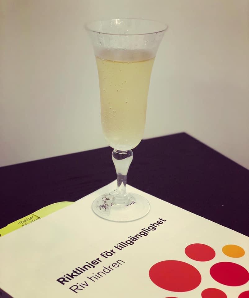 Boken Riv Hindren tillsammans med ett champagneglas. Fotograferat av tillgänglighetskonsult Anette Andersson, Nanyoung AB, när hon validerat sina kunskaper om tillgänglighet i vår validering.