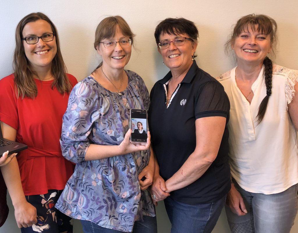 Fem ledamöter i styrelsen, varav en visas på en liten bildskärm