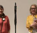 två damer framför ett konstverk