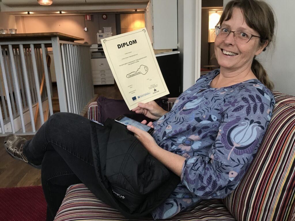 tillgänglighetskonsult Christin Jönsson ler glatt och visar upp sitt diplom efter slutförd validering.